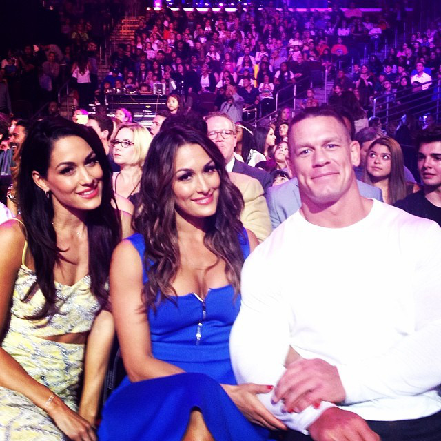 John Cena with Nikki Bella (in blue), alongside her twin sister, Brie Bella via eonline.com