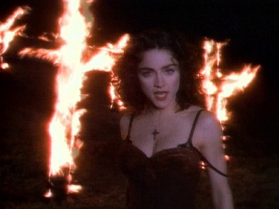 Madonna dancing in front of burning crosses in her
