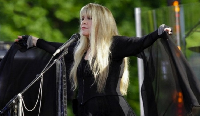 Stevie Nicks in concert showcasing one of her traditional accessories, a shawl  image via ABA